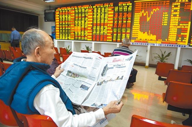 海口某證券交易大廳的股民在大盤前看報。(中新社資料照片)