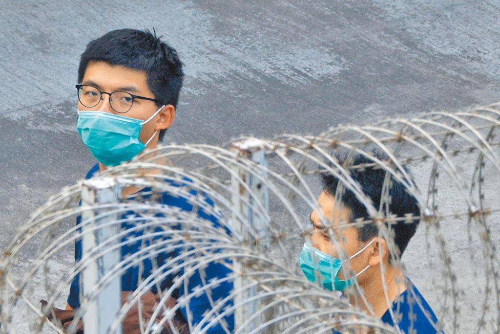 前香港眾志祕書長黃之鋒(左)因涉嫌觸犯《香港國安法》,7日在獄中再次被捕。圖為上個月3日黃在荔枝角收押所。(路透)