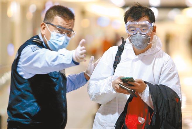 在桃園機場入境管制區內,身穿防護衣的旅客在防疫人員引導下,準備通關入境。(范揚光攝)
