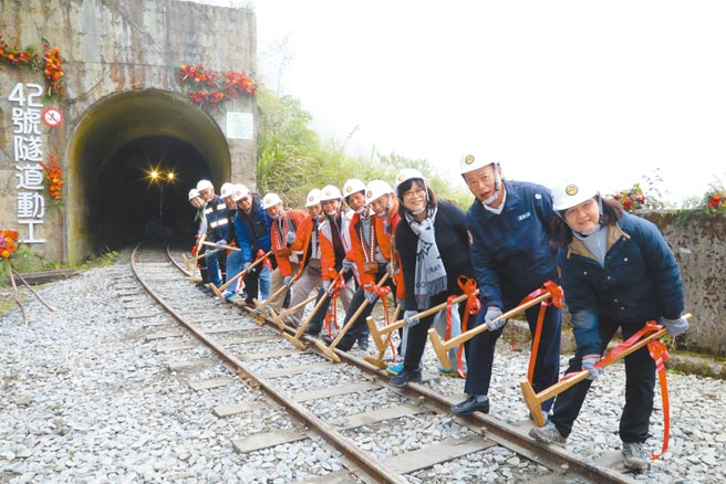林鐵及文資處邀請出席的貴賓手拿金鐵鎚,釘上保護林業鐵路軌道安全的「道釘」,象徵工程「鐵釘成功」。(張亦惠攝)