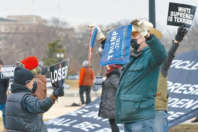 一名來自新澤西州的川粉(右)8日在華府國會山莊附近,與一群要求罷免川普的婦女對嗆。(美聯社)