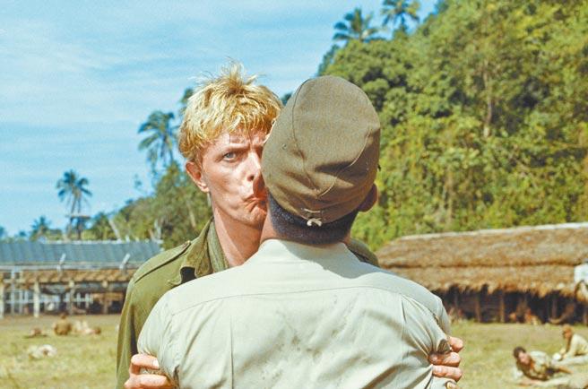 大衛鮑伊(左)與坂本龍一在銀幕上的驚天一吻,在保守的80年代引起軒然大波。(甲上娛樂提供)