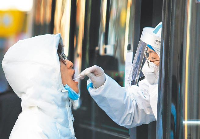 1月7日,醫護人員在「核酸採樣流動車」內為民眾進行核酸採樣。(新華社)