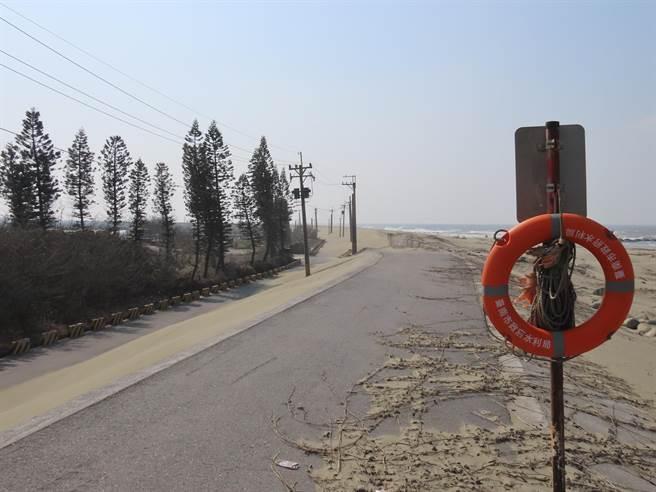 北門保吉里的海埔養殖專區每逢冬季,風沙越過海堤,掩蓋住防汛道路,阻礙通行。(莊曜聰攝)