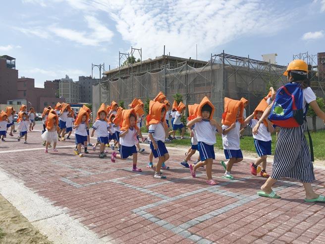 小學生們在老師引導下,戴上防震頭套演練地震逃生流程。圖/本報資料照片