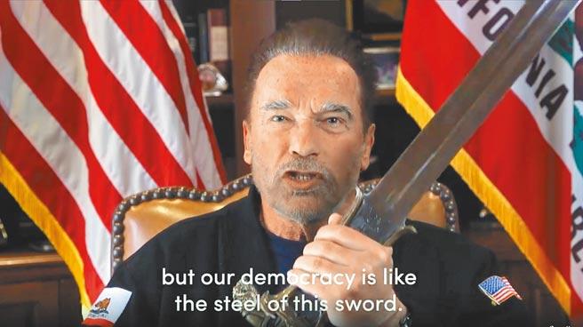 前加州州長阿諾史瓦辛格拿出38年前拍攝電影的《王者之劍》,表示美國民主猶如千錘百鍊的寶劍,愈鍛鍊就愈強大。(美聯社)