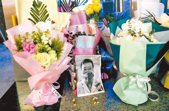 去年2月7日,在李文亮生前工作過的武漢中心醫院後湖院區門診樓門口,擺放著他的黑白打印照片和祭奠鮮花。(中新社)