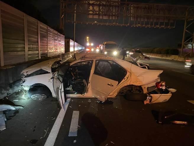 白色轎車自撞高速公路水泥護欄,並連續翻滾9圈,車身嚴重扭曲變形,幾乎變成廢鐵。(民眾提供/王文吉台中傳真)
