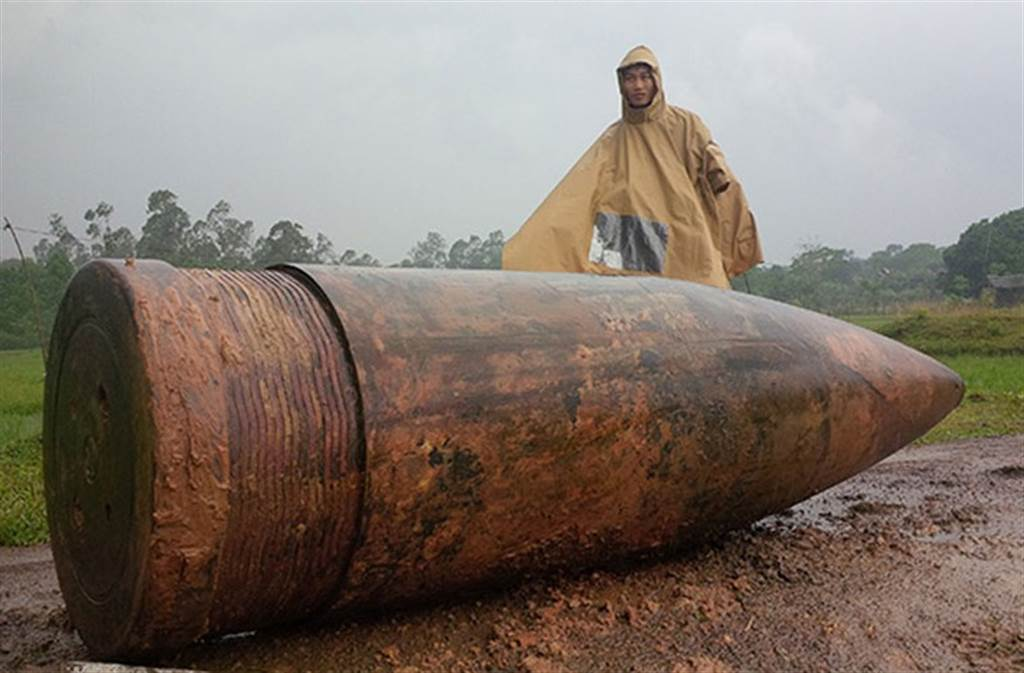 越南一人家从田地�e挖到近1吨重的战舰�h弹。(图/twitter)