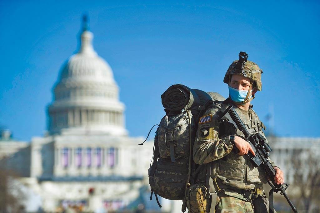一名荷槍實彈的美國國民兵13日在首都國會大廈前警戒。當天,國會眾議院就彈劾川普總統案投票表決。本月20日總統當選人拜登即將就職,為避免國會暴亂事件重演,華府已部署重兵嚴加戒備。(路透)