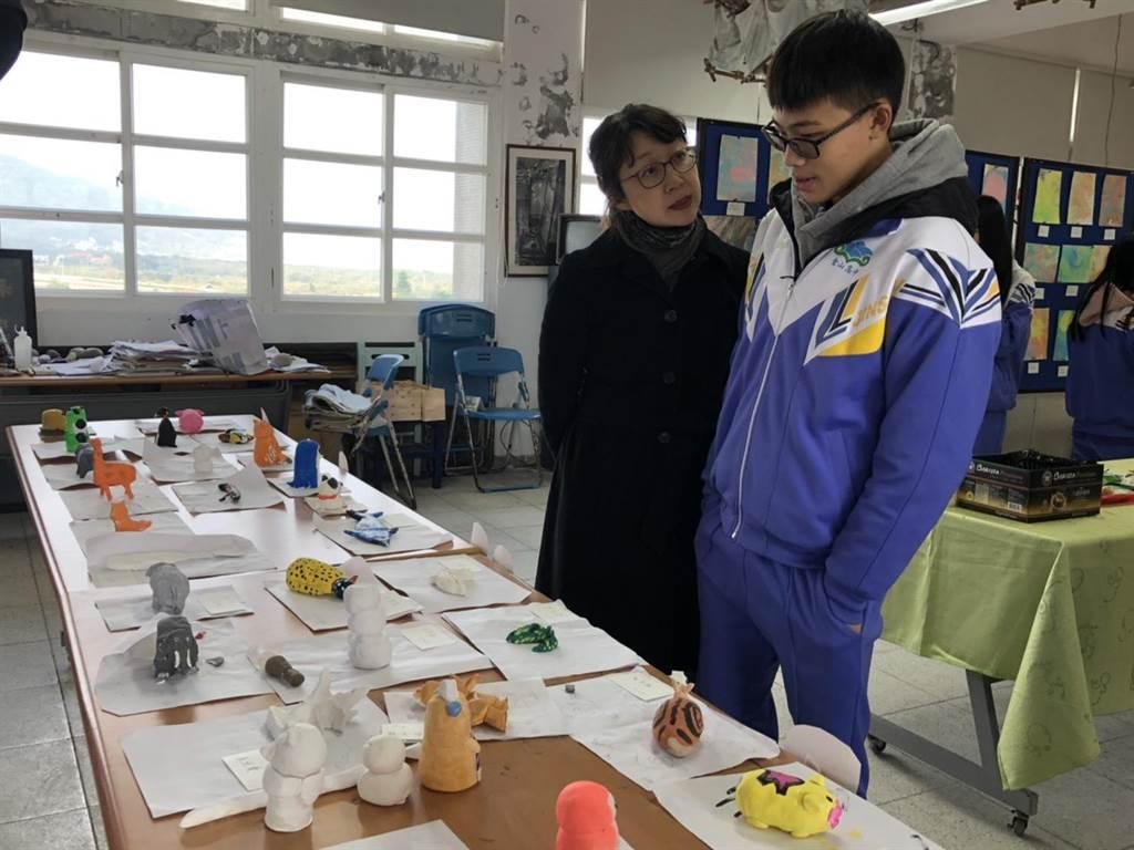 華梵大學美術與文創學系聶蕙雲副主任(左)與金山高中學生討論作品。(華梵大學提供)