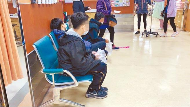 新北市大豐國小到台南、嘉義畢業旅行,14日疑發生集體食物中毒,身體不適的學童坐在急診室,對著塑膠袋嘔吐,臉色發白,顯得虛弱。(廖素慧攝)