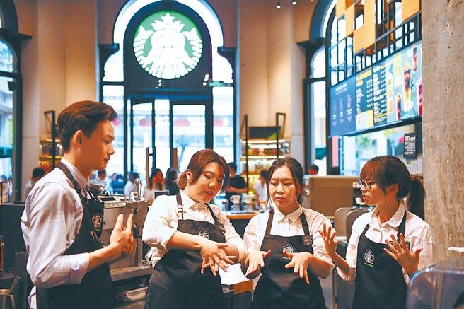 星巴克一直是全球連鎖咖啡領頭羊,更積極經營中國市場。圖為星巴克員工在進行手語練習,為聽障顧客提供服務。 (新華社)