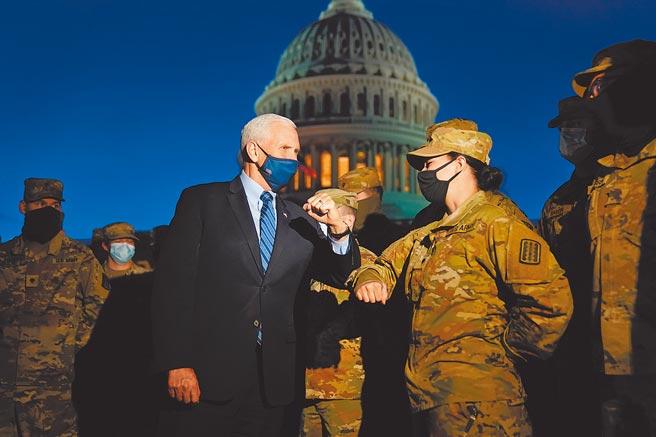 美國總統當選人拜登20日就職,華府進入高度戒備。圖為副總統彭斯巡視部隊。(美聯社)