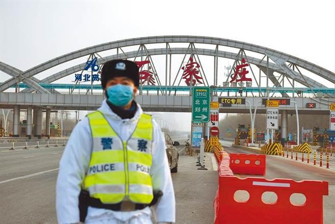 大陸新冠疫情持續蔓延,17日新增109例確診。 圖為一位民警在河北省石家莊裕華高速公路入口執勤。(中新社)