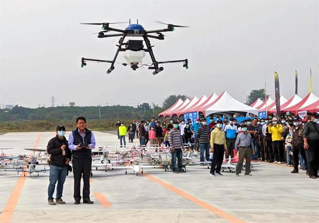 屏東竹田無人機飛行場17日啟用,屏東縣長潘孟安(左二)已取得遙控無人機學習操作證,在教練陪同下操作農噴無人機升空。(潘建志攝)