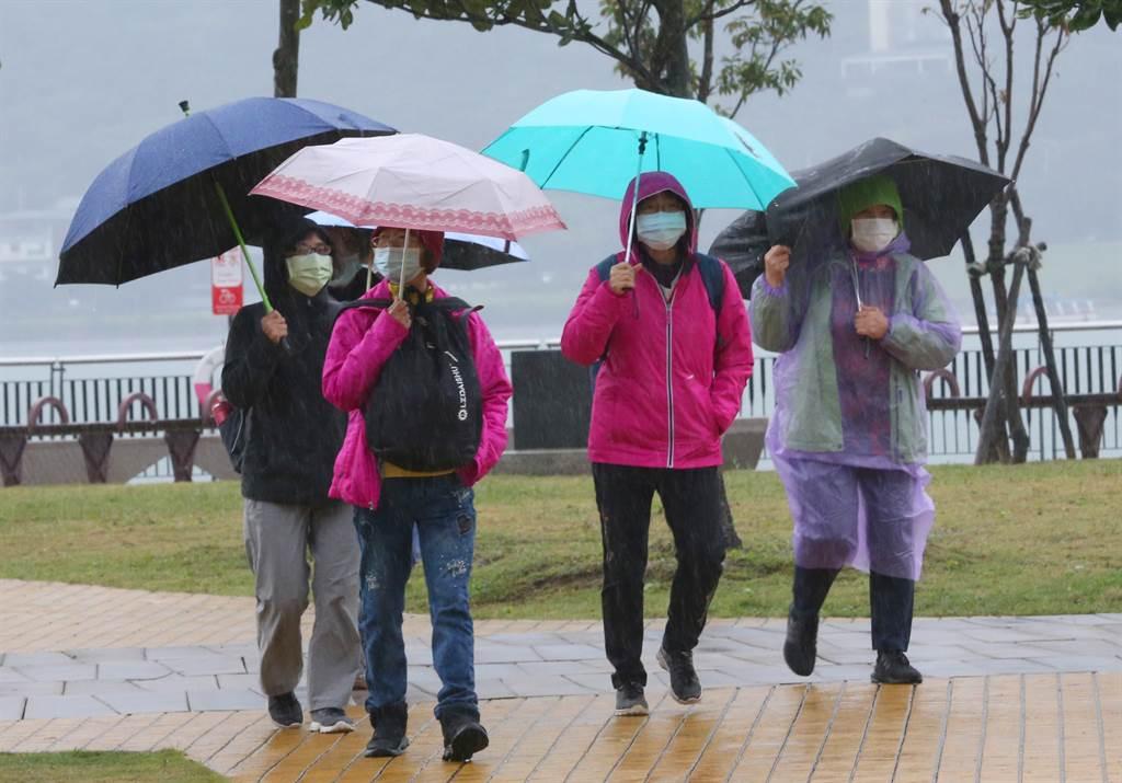 第4波恐周六報到,北台灣降至10度。圖為新北市淡水有民眾在寒冷的天氣撐傘到河邊散步。(資料照 陳君瑋攝)