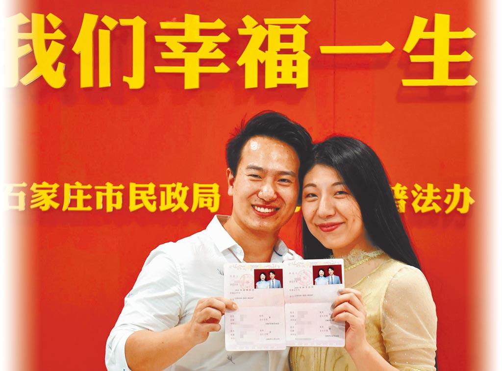 大陸江浙一帶興起新興的「兩頭婚」,夫妻雙方家庭在婚姻中地位平等,符合年輕一代的性格特點。圖為一對新人領取結婚證後拍照留念。(新華社)