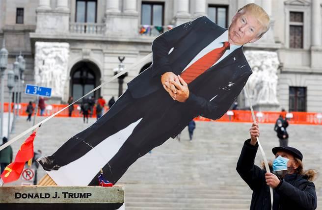 一名反川人士1月17日在賓州首府哈立斯堡(Harrisburg)拉倒美國總統川普的人形立牌,以示抗議。(路透)