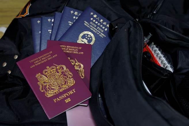 英國宣布新的海外護照政策,大量接納香港移民,預計5年內將有32萬港人移民英國。圖中藍色為香港特區護照,紅色為 英國海外公民護照。(圖/路透)