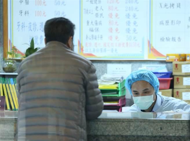 衛福部立桃園醫院五位醫護人員染疫,該院掛號部門同仁穿上消毒及戴上頭套防疫裝備上班。(陳怡誠攝)