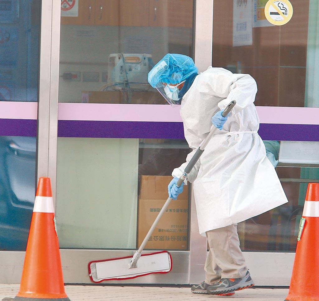 本土疫情升温,学者忧心衝击总体经济表现。图为清洁人员穿上防疫设备清洁环境。(陈怡诚摄)