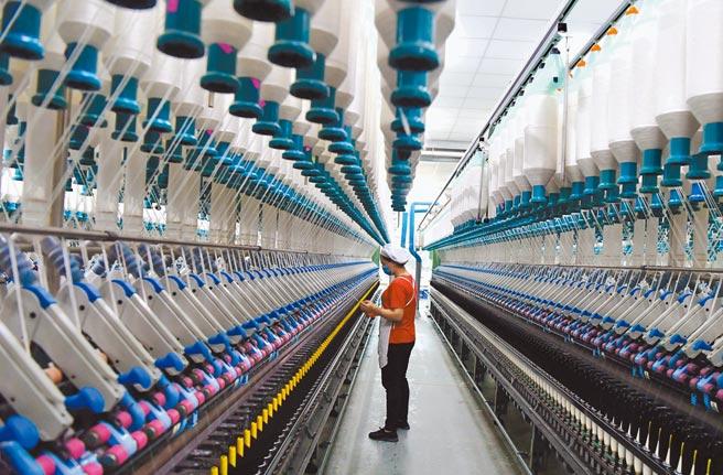 中國國家統計局公布,2020年GDP總量首次突破百兆大關、達101兆人民幣,比上年增長2.3%。圖為福建省長汀縣一家紡織廠內,工人在生產車間作業。(中新社)