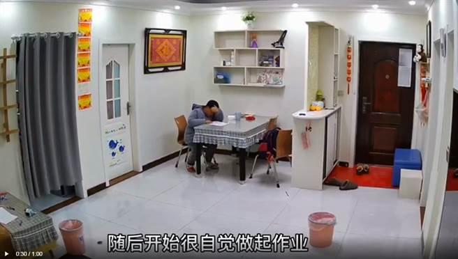 大陸江蘇連雲港市一名7歲男童,返家後開心地揮舞考卷,對著監視器鏡頭向母親報喜,沒有馬上得到回應,男童便乖乖在書桌上寫起作業。(圖翻攝自現代快報)