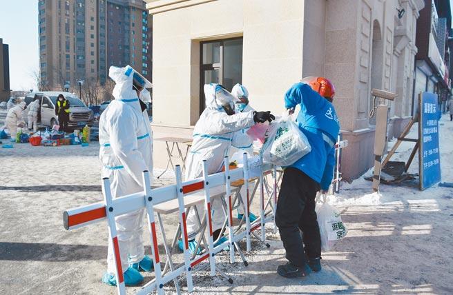 图为防疫工作人员为隔离居民运送生活物资。(中新社)