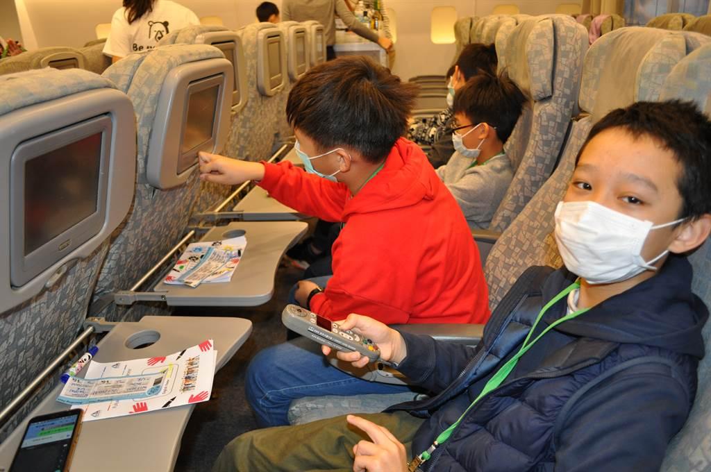 好久沒出國了,頭湖國小五年級學童謝暐振一登機,就忙著把玩飛機影音娛樂遙控器。(醒吾科大提供)