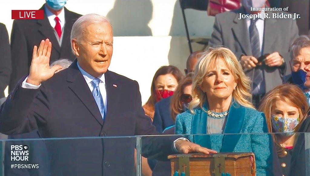 拜登就任美国总统典礼20日在华府国会山庄登场,拜登手按圣经宣誓就职。(摘自PBS直播)