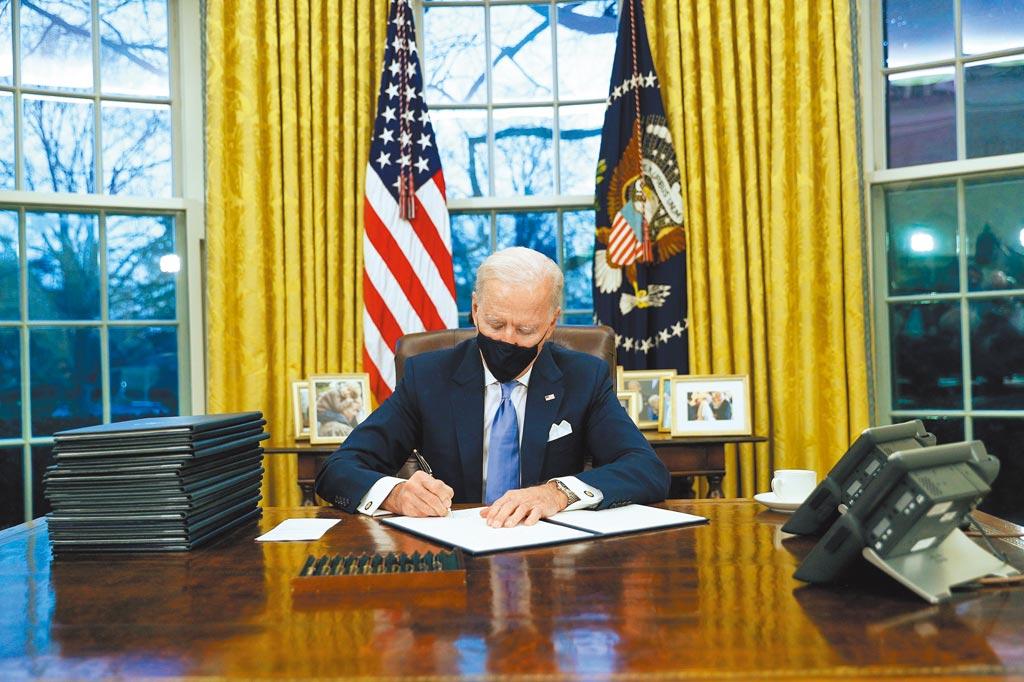 美國總統拜登20日就職後,當天即投入工作。圖為拜登在白宮橢圓形辦公室內簽署行政命令。拜登的命令推翻川普政府多項政策,如重返世衛組織、終止興建美墨邊境圍牆等。(路透)