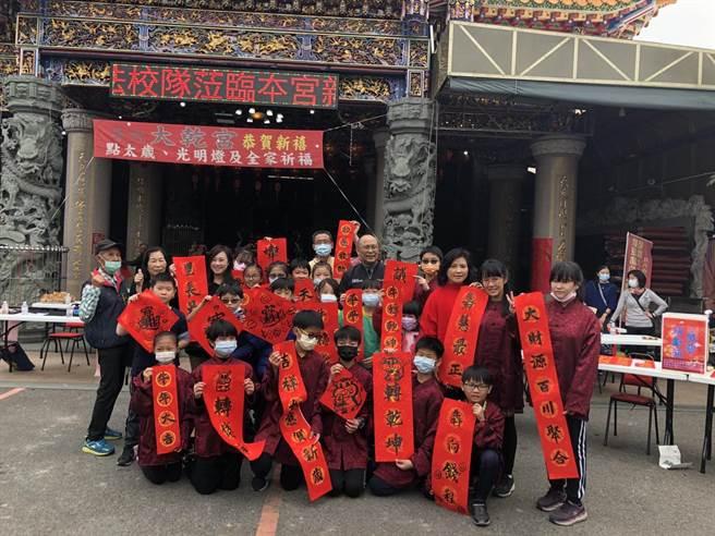 斗六市公誠國小書法隊學生到學區內的大乾宮義寫春聯。(縣議員王又民提供)