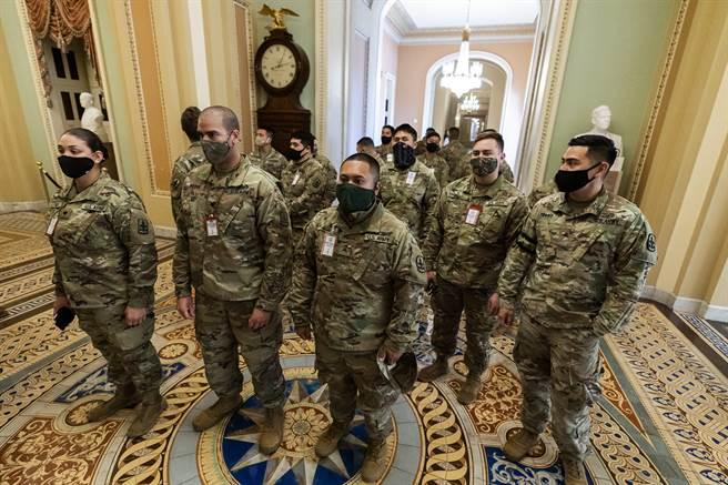 美國前任總統川普的支持者本月6日闖入國會大廈後,當局在華府採取前所未見的維安措施,包括架設有刺鐵絲網的圍欄以及國民兵(National Guard)檢查站。(圖/美聯社)