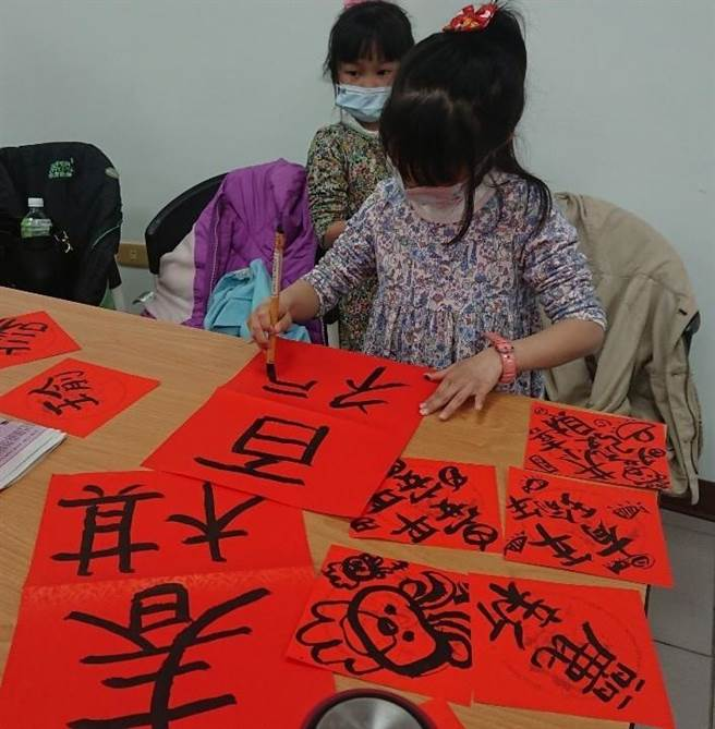 小朋友在紅紙上寫寫畫畫,體驗年節的熱鬧氣氛。(移民署金門縣服務站提供)