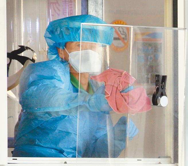 部立桃園醫院爆發院內群聚感染,疫情指揮中心表示,目前社區沒有擴大感染跡象,民眾無須過度恐慌。圖為在桃醫急診室外,工作人員正忙著清潔消毒。(范揚光攝)