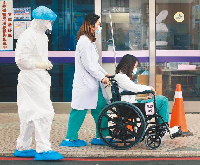 在部立桃園醫院急診室外,醫護人員22日陪同1名身體不適的同仁就醫。(范揚光攝)