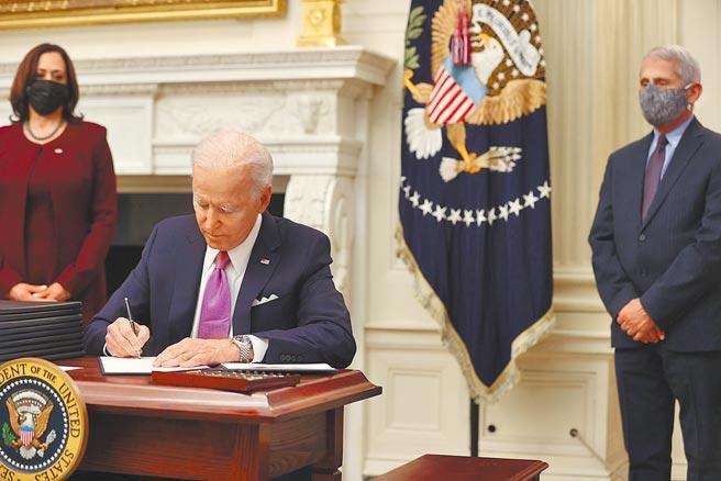 美國總統拜登21日簽署應對COVID-19的行政命令。(路透)