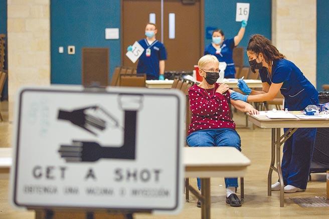 在美國德州一座大型疫苗接種中心內,護士21日為一名老婦人注射莫德納(Moderna)新冠疫苗。美國已有超過40萬人死於新冠肺炎,總統拜登上任後立刻快馬加鞭展開抗疫行動。(美聯社)