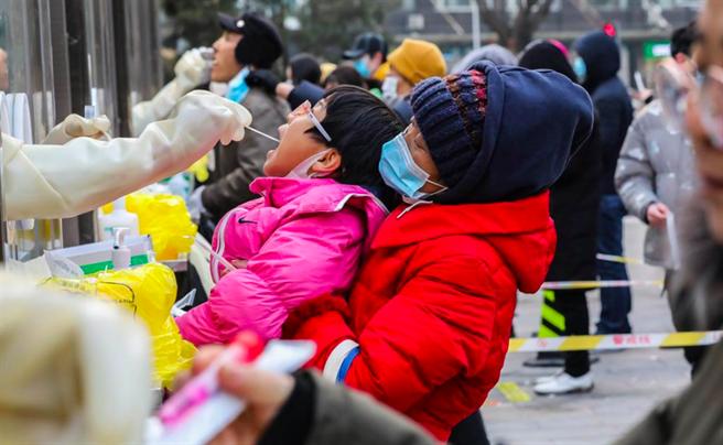 北京东西城组织区域内全员核酸检测,图为在位于北京市西城区广外街道的一处临时核酸检测採样点,来自中国中医科学院广安门医院的医护人员为一名小朋友採集核酸样本。(新华社)