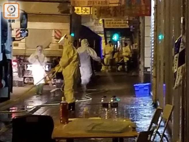 工作人員穿著防護衣,清洗街道。(圖/摘自東網)