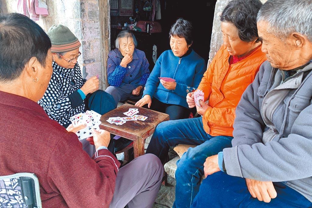 大陸陷入20年來出生率最低、老齡化加劇的困局。圖為安徽省一農村,老年人在家門口打牌消遣。(中新社)