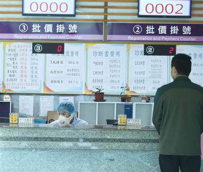 25日,中老年患者前往桃醫拿藥,掛號櫃台的工作人員穿戴防護設施服務病患。(陳怡誠攝)