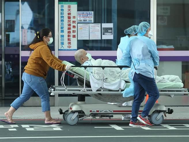 25日,一名重症病患由醫護人員推著病床自門診中心轉至急診中心。(陳怡誠攝)