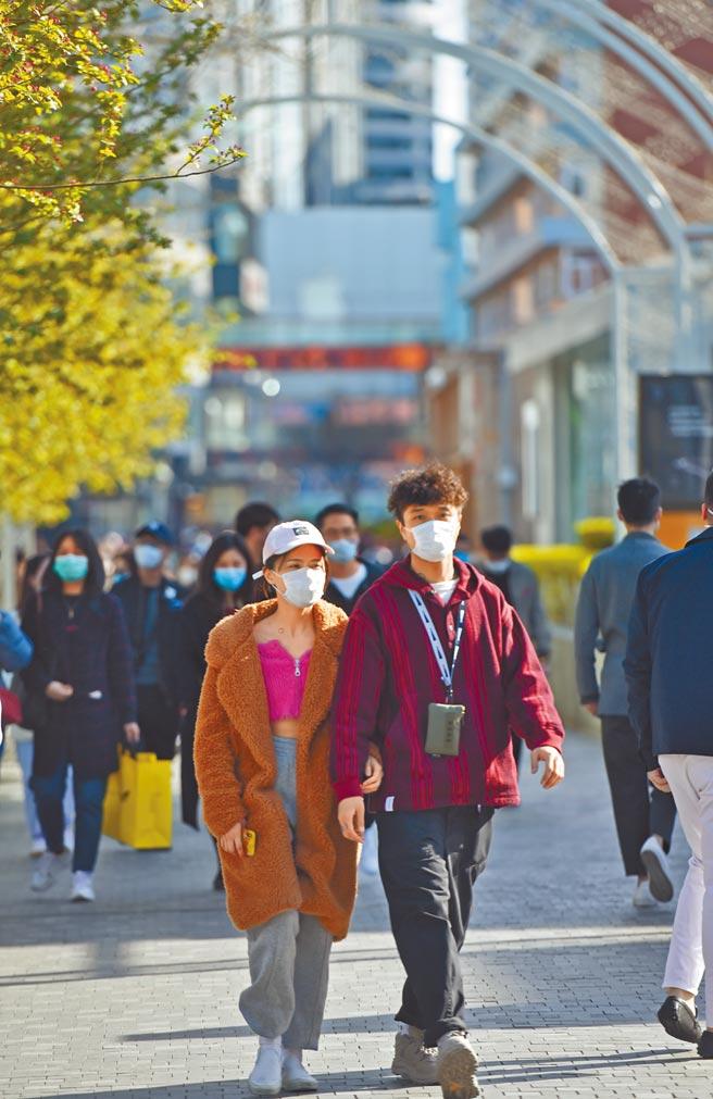 儘管開放二胎,大陸結婚率、生育率仍下降。圖為一對情侶漫步在北京三里屯商圈。(新華社)