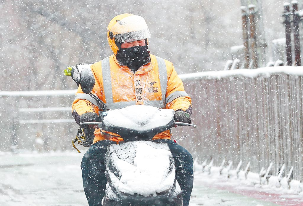 2020年7月,美團(大陸零售、外送平台)發布《2020上半年騎手就業報告》,內容指出超過50%以上外送員每月有人民幣4000元以上收入,圖為外送員在雪中送餐。(中新社)