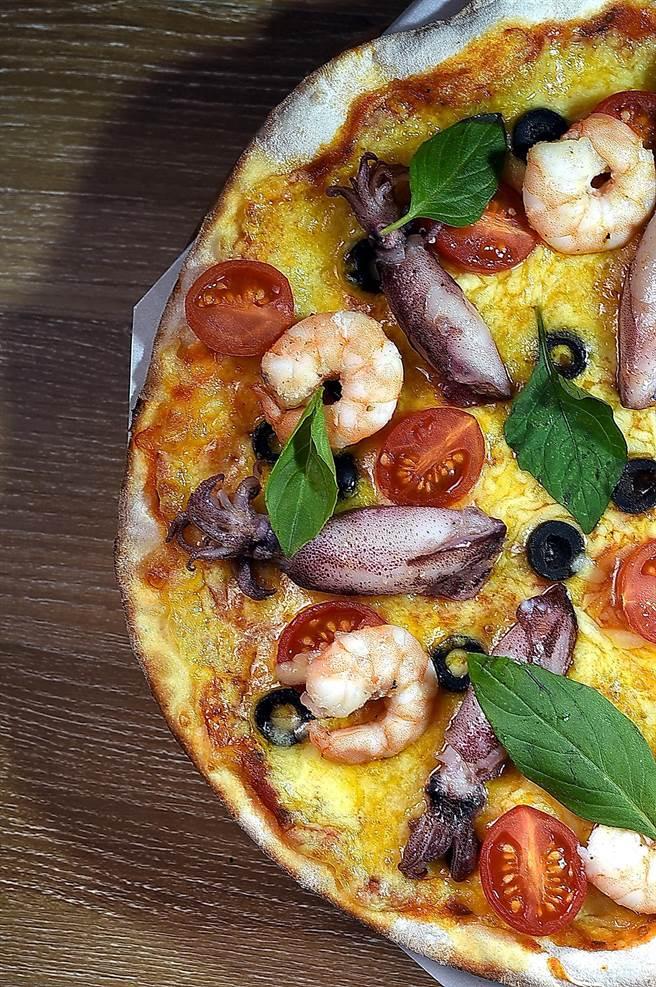 〈Pino〉的〈漁港海鮮披薩〉餡料有蝦仁、小卷、黑橄欖、小番茄、九層塔,以馬芝瑞拉和切達兩種起司。(圖/姚舜)