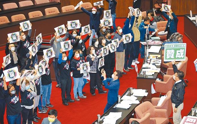 圖為去年底立院萊豬攻防,藍委高舉「民主進步黨-騙」標語。(本報資料照片)