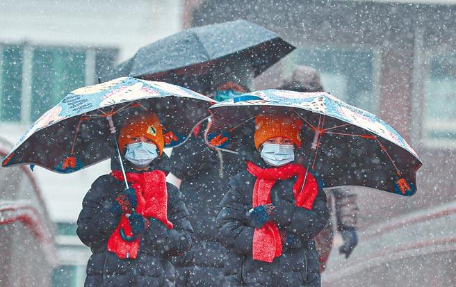 1月25日,北京迎來2021年第二場降雪,市民打傘出行。(中新社)