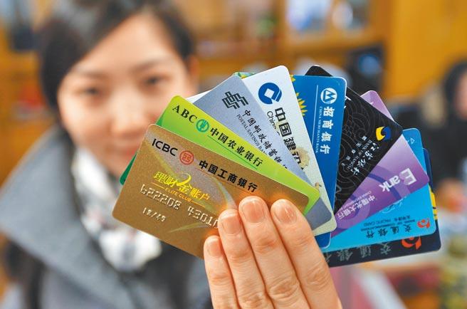大陆网上有各种形形色色的贷款花招。图为一位南京市民展示拥有的多家银行卡。(中新社)
